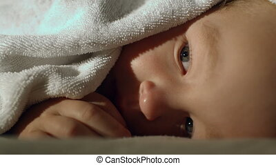 Little boy covered with the towel