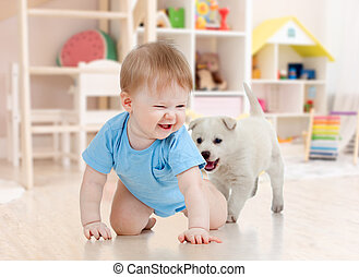 Little boy crawling and playing with adorable puppy at home