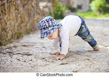 Little boy crawling on stone paved sidewalk - Cute little...