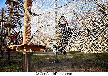 little boy crawling on suspension net bridge. horizontal...
