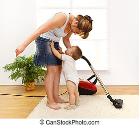 Little boy crying to be picked up - Mother cleaning the ...