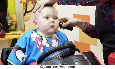 Little boy cuts the barber. He sits in a chair that looks like a car.