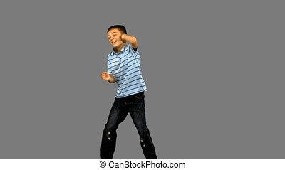 Little boy dancing on grey screen in slow motion