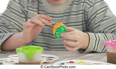 Little boy decorating easter eggs