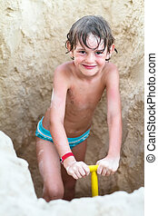 Little boy digging in the sand on a tropical beach