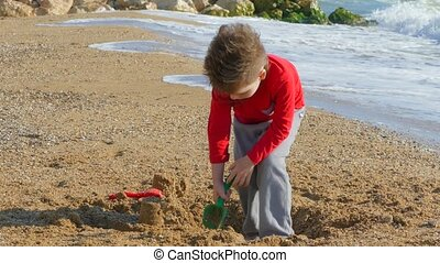 Little boy digging sand on the beach