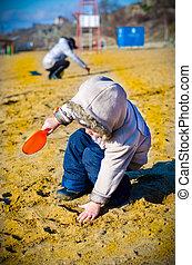 little boy digs in sand