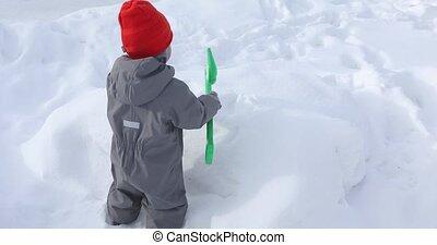 Little boy digs with shovel snowdrift - Cheerful child digs...