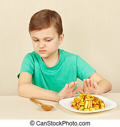 Little boy does not want to eat fried potatoes