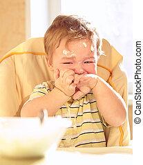 Little boy doesn't want to eat porridge.