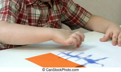 Little boy doing finger painting