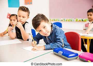 Little boy doing some math at school