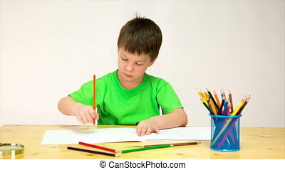 Little boy draw with pencils at the table