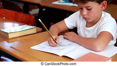 Little boy drawing in notepad in classroom in elementary...