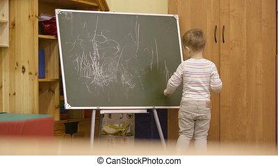 Little boy drawing on a chalkboard at kindergarten