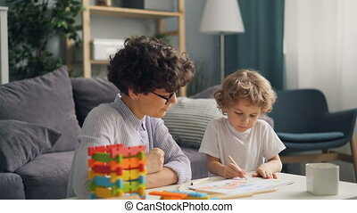 Little boy drawing with caring mommy at table in light room in studio apartment