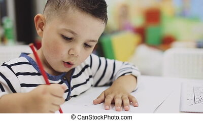 little boy drawing with colored pencils on paper