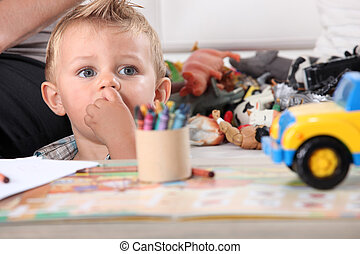 Little boy drawing with crayons