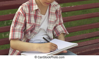 Little boy draws in his notebook on the bench