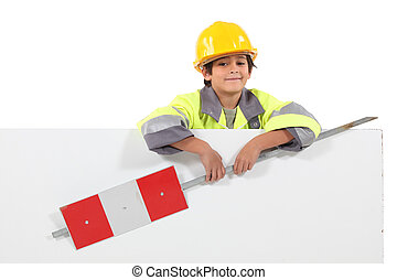 little boy dressed as a road worker holding a traffic sign