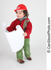 Little boy dressed as builder holding plans