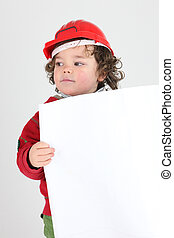 Little boy dressed as manual worker holding poster