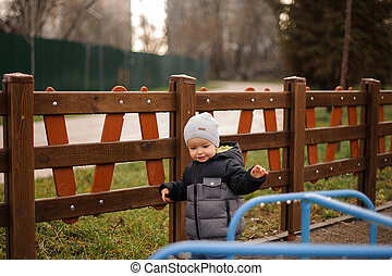 Little boy dressed in a warm hat and jacket on the background of wooden fence