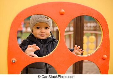 Little boy dressed in a warm hat and jacket on the playground