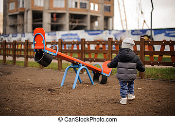 Little boy dressed in a warm hat and jacket on the playground with swings