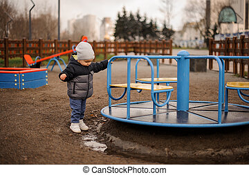 Little boy dressed in a warm hat and jacket playing near the carousel