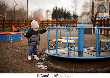 Little boy dressed in a warm hat and jacket standing near the carousel