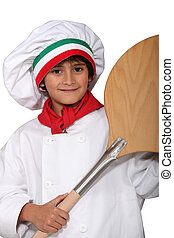 little boy dressed in pizza cook with a spade