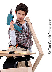 little boy dressed like a craftsman holding a drill