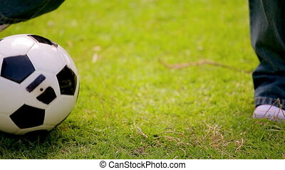 Little boy dribbling on the grass