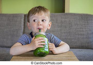 Little boy drinking a green smoothie - Cute little boy ...