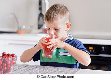 Little boy drinking fruit juice in a kitchen