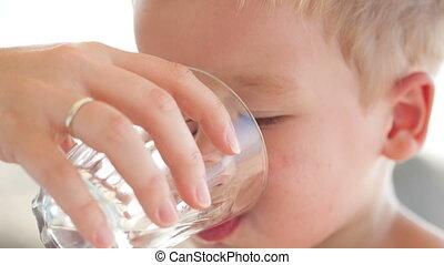 Little boy drinkng a glass of fresh water
