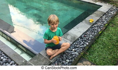 Little boy drinks fruit smoothie from a glass using a stainless drinking straw. Reduce the use of plastic. Shot on a phone.