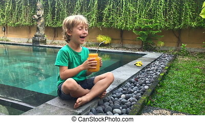 Little boy drinks fruit smoothie from a glass using a ...