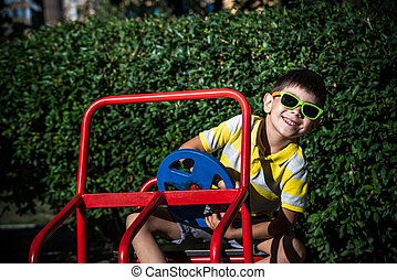 Little boy driving big toy car and having fun, outdoors