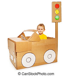 Little boy driving his handmade cardboard car