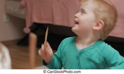 Little boy drumming playing with sister at home interior closeup