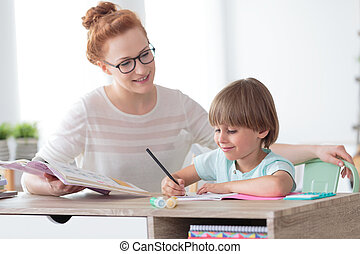 Education concept, smiling little boy studying with friendly young home tutor during private lesson after school