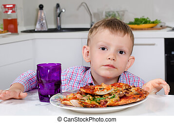 Little boy eating a big plate of pizza
