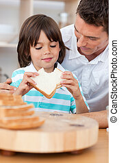 Little boy eating a sandwich with his father