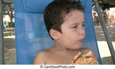 Little boy eating burger