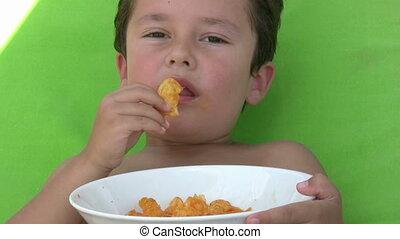 Little boy eating chips