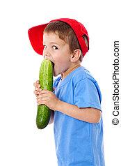 Little boy eating cucumber