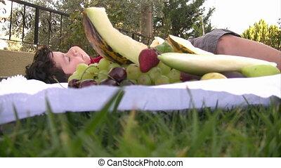 Little boy eating fruit at picnic o