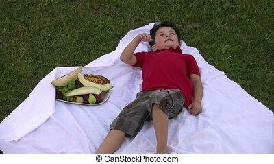 Little boy eating fruit